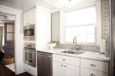 Reflection in Manchester-by-the-Sea. Faux pressed-tin tiles add a splash of silver to the kitchen walls in Jen and AJ Migonis' Massachusetts...