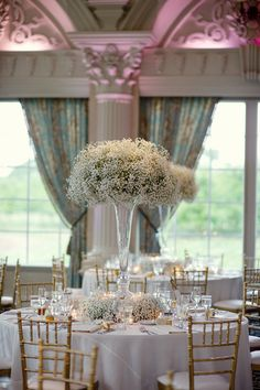 Tall trumpet vase with babies breath centerpieces - just another option for you. They look just incredible en masse