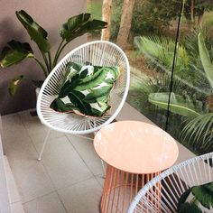 outdoor design: for small balcony, urban design, small apartment, white Acapulco chairs, peach side table, palm print cushions, palm trees