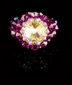 Champagne Swarovski Rivoli ring with Fuchsia and Cyclamen Opal Swarovski Bicones, Jet and Garnet AB rounds with Silverlined Amber seed beads
