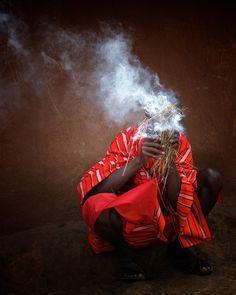 In a Masai village in Kenya, a Masai man blows to light a fire .