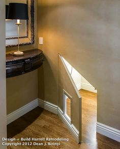 """A carefully hidden cat door under the stairs is quickly accessed by the homeowners with an angled door when the """"kitty litterbox"""" is ready to be changed."""