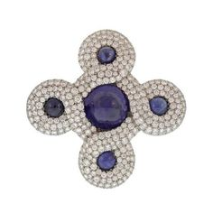 CHANEL A distinctive Chanel brooch designed in the shape of a traditional Celtic Knot. One large, and four smaller intense blue cabochon sapphires are set in platinum, surrounded by glittering diamonds that pave an eternal curving maze.1980s