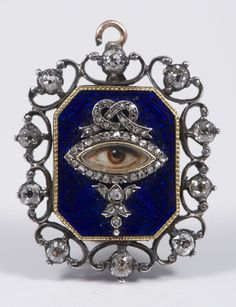 Fine Georgian yellow metal and silver diamond pendant with central blue guilloche enameled octagonal panel decorated, with an ivory painted eye in diamond designed mount, surrounded by ten diamonds in open scroll claws.