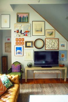 Love when the tv is surrounded by art. Good examples in post. Also great use of the odd shape walls stairs create.