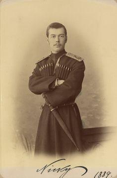 Tsarevich Nicholas, depois, Tsar Nicholas II (Czar Nicolau II). Ele está em pé de frente para a câmera com os braços cruzados. Ele está vestindo o uniforme da própria comitiva de Sua Majestade Imperial e tem uma espada na cintura. A fotografia foi assinada e datada 'Nicky 1889'.