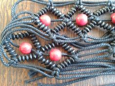 Black macramé cord belt with red wooden beads and fringes, in perfect condition.