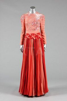 Valentino couture evening gown, circa 1985-8, un-labelled, of deep peach crêpe, the bodice covered in swirls of bugle beads and rhinestones, the skirt formed from pleated interwoven godets of chiffon in shades of deep wine to peach. Front