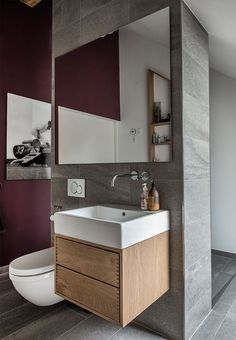 Custom made wooden furniture under the zink, that matches the raw and natural look from the gray tiles and aubergine coloured walls.