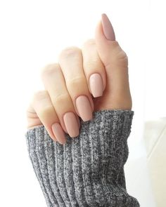simple powder pink nude nails, with squoval shape, on a hand with folded fingers, in a long grey knitted sleeve