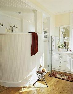 In this bath, vintage charm comes in the form of antique random-width wood flooring salvaged from a local barn.