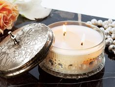 A gorgeous replica of a vintage powder puff box, this decorative 8 ounce glass vessel is filled with soy wax scented with sweet grapefruit, ginger and Himalayan spices. Topped with an etched metal lid, candle burns approximately 40 hours and comes gift wrapped in a hand crafted wood crate with ribbon.