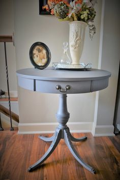 The table itself is round on top, with a pedestal base and four elegant legs that curve outward and are finished off with metal claw feet. Description from etsy.com. I searched for this on bing.com/images