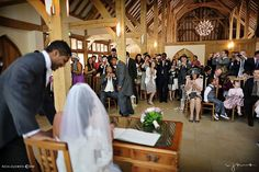 Guests taking photographs of bride and groom signing the register at Rivervale Barn