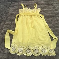 Adorable yellow sundress Perfect for summer, this bright yellow dress has beautiful eyelet flower design at top and bottom hem. Empire waist with back tie. Can be worn with or without straps (by tucking straps in). Excellent condition. Fully lined. Dresses
