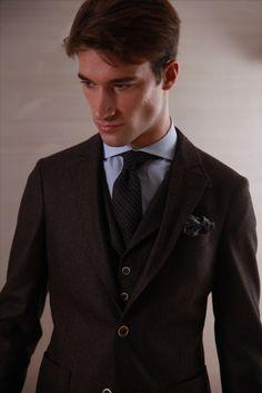 Cravate en laine motif Prince de Galles brun sur une chemise en coton double retors à petits carreaux fenêtre bleu. Ici accessoirisés d'un mouchoir de poche beige, brun et bleu. #WicketSoBritish