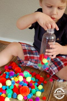 Fine motor play with a pompom bottle!