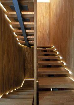 Det er felt inn lys på siden av trinnene. Dette gir utrolige lysvirkninger i trapperommet. Veggene er kledd med massive eikeplater.