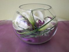 Modern centrepiece goldfish bowl featuring entwined calla lilies with bear grass.  The bottom of the goldfish bowl is lined with organza and silver pebble chips.  Purple faux jewels have also been added to the design.