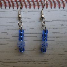 """Use the coupon code WEAREOPEN to save 10% on orders of $15 or more at checkout thru Sept 30th for our GRAND OPENING!.....   Stainless steel hook earrings with blue glass """"E"""" beads and a round acrylic clear  disc with a blue flower design in it."""