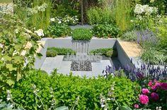 Derrière des murs gris, un espace dédié avec une salle à manger et aussi une cuisine d'extérieur, ce jardin est entouré d'une riche et colorée végétation.