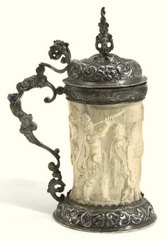 AN IVORY TANKARD WITH PARCEL-GILT SILVER MOUNTS, PROBABLY GERMAN, 19TH CENTURY carved ivory sleeve with the Triumph of Bacchus, masks, acanthus and shells at the hinged cover, neck and detachable foot, unmarked.