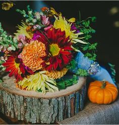 colorful fall colors wedding bouquet on tree slab stand.