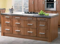 Walnut Kitchen Cabinets In The Island With Modern Knobs And Stainless Steel Countertops