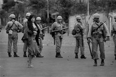 Iranian woman in front of soldiers during 1979 revolution, Tehran, Iran.