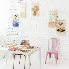 Maryanne Moodie's weaving studio in Brooklyn with white painted exposed brick wall, weave hanging on walls, and a white desk filled with weaving accessories