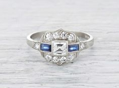Antique Art Deco ring made in platinum and centered with an approximately .50 carat step cut diamond. Accented with baguette cut sapphires and old European cut diamonds. Circa 1920.