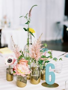 Love the gold dipped jars for the arrangements! | Bright, colorful Colorado wedding: Taylor + Justin