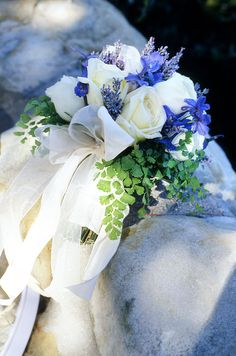 Touches of purple wildflowers with white roses make this a great bridesmaid bouquet for an outdoor wedding