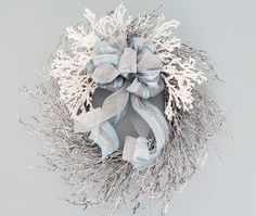 Beach decor Christmas wreath with faux coral in elegant and icy blue. This fabulous coastal holiday wreath is simple and elegant, handmade on a wreath form that is PVC coral-like branches. We add intricately beaded white faux coral branches and then a fabulous over the top wired bow with long tails that you can curl how you like. The ribbon is high end and drop dead beautiful, double layered ice blue with mesh and a solid silver mesh that perfectly coordinate.