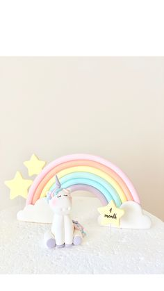 Cute unicorn made of edible fondant, with rainbow in pastel colors. Made by Alex from Sugar Bear Studio