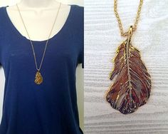 Necklace details:  • Pendant is antique gold-colored feather made of zinc alloy metal • Pendant is 2 in height and 1 in width • Chain is gold-plated tiny flat soldered cable chain 1.6mm • Necklace is 30 with 2 extender chain and lobster clasp closure • Lead safe, nickel safe • Base metal of chain is brass  Other information:  • Every purchase from our shop supports nature-related organizations • This necklace is part of our Into the Woods collection, and supports rainforest conservation in…