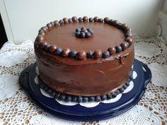 Mega chocoladetaart gevuld met chocomousse en blauwe bessenjam, topping van ganache.