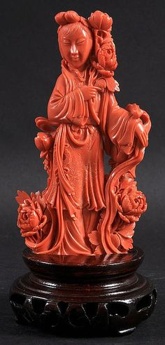 Description: A GOOD EARLY 20TH CENTURY CHINESE CARVED RED CORAL FIGURE OF A FEMALE modelled holding a floral sprig, wearing incised foliate robes. Tiny nicks to flowers. Coral 6ins high.