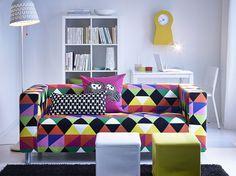 Ein Wohnzimmer mit 2er-Sofa mit buntem Bezug aus Baumwolle und zwei Hockern in Weiss und Gelb