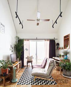 층고 높은 천장 아래 실링팬을 달고 부부를 위한 아늑한 라운지체어로 꾸민 거실.