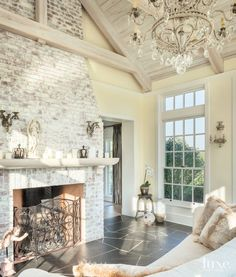 A crystal chandelier brings a touch of elegance to the solarium, which was designed as a retreat for homeowner Angela Kroeger. The fireplace is part of the same whitewashed brick massing used in the kitchen, and the fireplace screen features more of the o House Design, New Homes, House Plans, White Wash Brick, House, Home, Fireplace, Luxe Interiors, Brick Fireplace