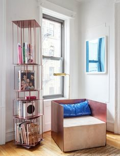 """Harry describes this corner as """"like a small library,"""" with a towering bookshelf and a chair of his design from the Sight Unseen show that brought him here. """"I love how the two colors play with each other—the electric blue and this elegant, naked skin color,"""" he says. """"It was by accident, I didn't know the two colors would work!"""""""