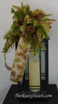 Our floral swags are a great way to dress up a lantern, candlestick, wreath, banister, and more! This swag is made with faux burlap ribbon with pinecone print, pinecones, gold accents, and various greens. They are versatile and can be used in so many different ways! The swag measures approx. 9.5 W x 15L. They simply attach with wired chenille. Lantern is NOT included in sale.   *Please note our handmade items may vary slightly.  ***Swag is shown on lantern measuring 20H x 8.5W x 8.5D***   We…