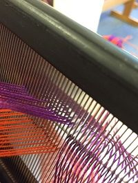 Threading the loom with two ends per dent, with a divided reed to keep the warps from twisting between reed and heddles.