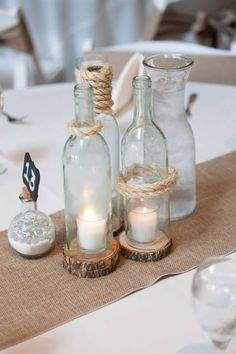 Wine bottles with the bottom cut out and rope tied around them.. With wood discs underneath wedding centerpiece :)