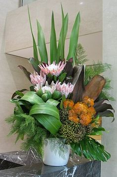 .Full arrangement with height and width flower arrangement protea, leaves, fern,