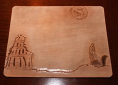 "A leather mouse pad.  A freehand representation of ""The Lighthouse"".  A coyote bays at the moon in the foreground.  The coyote was transferred with a stencil and given hair with tooling for realism."