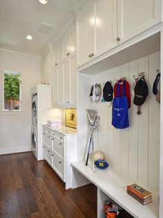 This mudroom and laundry room combination space features hooks and a bench seat for hats, bags and shoes as well as plenty of crisp, white cabinetry for laundry supplies and extra linens and towels. The stacked washer and dryer takes up minimal space, leaving room for an adjacent countertop workspace.