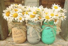 Painted Mason jars finished with twine and filled with daisies.