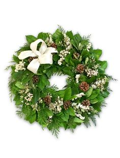 Our Winter Forest White Wreath features fragrant cedar and fresh salal leaves form a verdant backdrop upon which ivory-edged rhamnus leaves, fresh white larkspur, tallow berries, and achillea of the pearl perch like newly fallen snow.